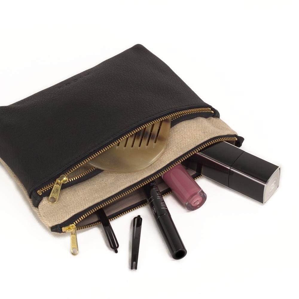 Das ist Kosmetiktasche Ida in Natur und Schwarz gefüllt mit Kosmetik.